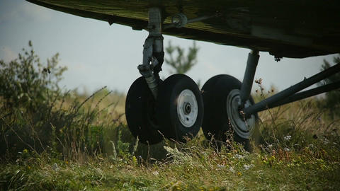 Closeup Helicopter Landing Gear Lands on Field Wind Shakes Grass Footage