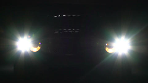 Car headlamps switch on and off in darkness, bright headlight illumination Footage