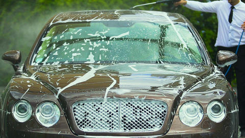 Businessman's driver washing luxury car with water spray gun for business trip Footage