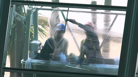 Cleaners washing windows of high rise building, risky occupation, life danger Footage