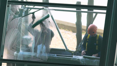 Brave high rise workers cleaning window glass, dangerous trade, risk to health Footage