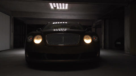 Professional driver testing new expensive car in garage, switching on headlights Footage