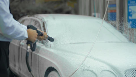 Expensive carwash, male dressed in suit washing car with cleaning foam, business Footage