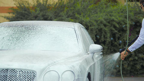 Chauffeur washing luxury automobile with suds, responsible work, business Footage