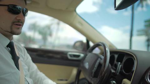 Businessman wearing sunglasses driving expensive automobile, transportation Footage