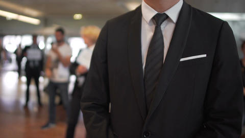 Man in business suit waiting for arrivals in airport hall, travel agent, tourism Footage