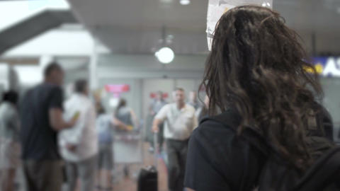 Female tourist guide standing in airport, waiting on guests, holding name sign Footage