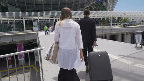 Glamorous female and bodyguard with her luggage walking at the airport, tourism Footage