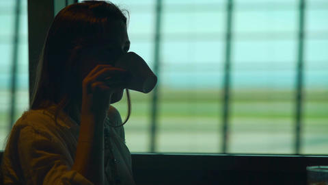 Thoughtful female drinking coffee at the airport and waiting for her airplane Footage