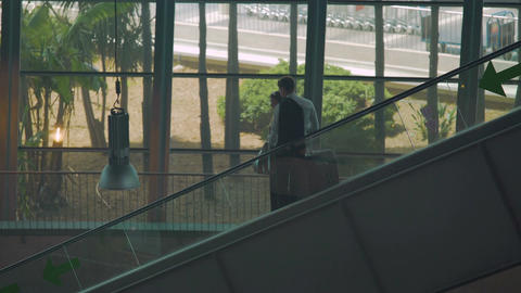 Couple of business partners moving on escalator in airport, arriving for meeting Footage