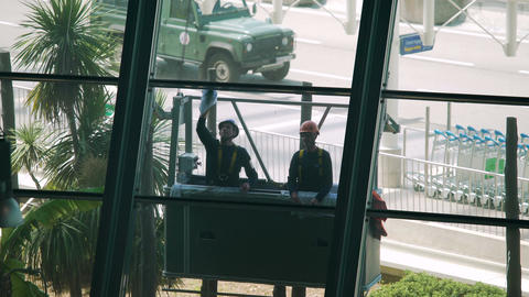 Cleaning service, two male cleaners washing windows in airport, physical labor Footage