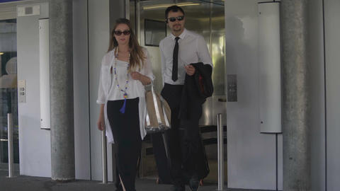Business trip, man and woman exiting elevator with hand luggage, tourism Footage