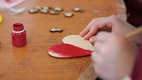 Girl's hands painting wooden heart at craft and maker class, handmade, hobby Live Action