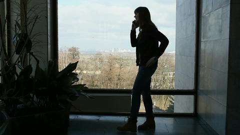 Long-haired brunette woman standing near big window and speaking on the phone Footage