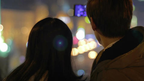 Man and woman photographing themselves on smartphone, relaxing evening in city Footage