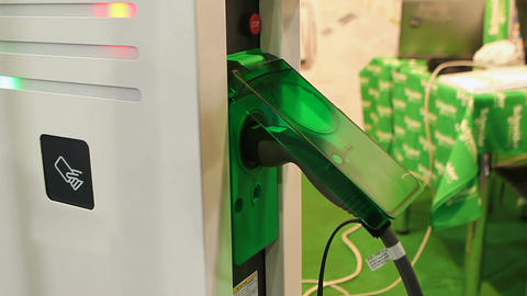 Consultant presenting latest charging point for electric vehicles at exhibition Live Action
