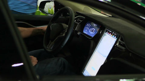 Male driver inside of modern electric auto stuffed with advanced technologies Live Action
