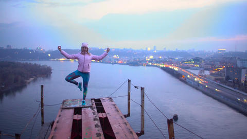 Young woman in standing asana on the edge of bridge, yoga practice, adrenaline Footage