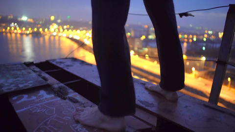 Barefoot man standing on bridge edge, thinking about suicide, changing his mind Footage
