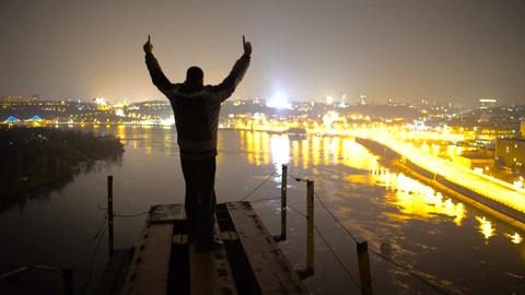 Pleased man looking at night city from top of bridge, raising his hands, victory Footage