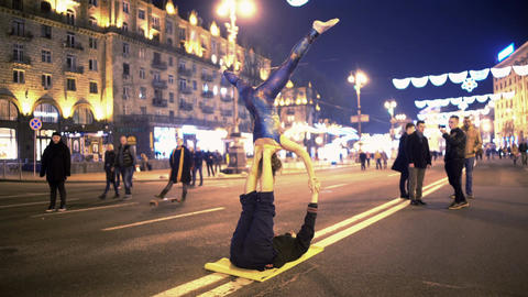 Young couple making dangerous tricks in public place, acro yoga performance Footage