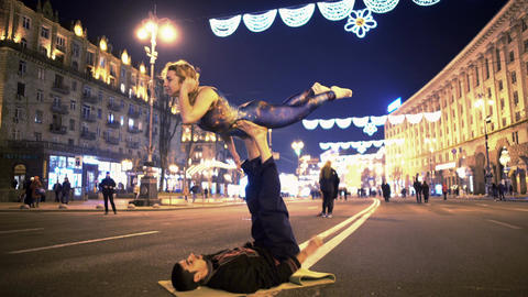 Smiling sporty couple practicing acro yoga poses on the street, extreme hobby Footage