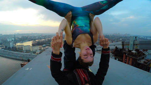 Two athletes doing acro yoga exercises on bridge, risky hobby, extreme sports Live Action