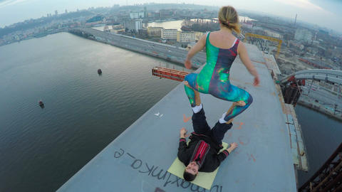 Extreme sport, female balancing on male legs on top of bridge, dangerous hobby Footage