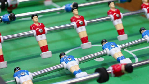 Table football, plastic figures of soccer players moving on foosball field, pub Footage