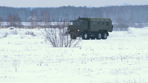 Military truck crosses a snowy field Footage