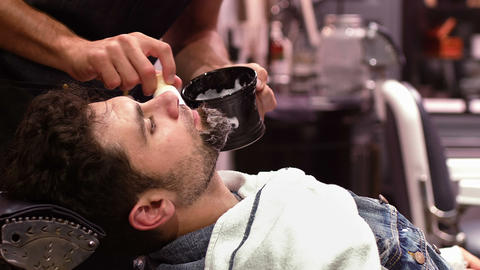 Man getting his beard shaved with shaving brush in barber shop Footage