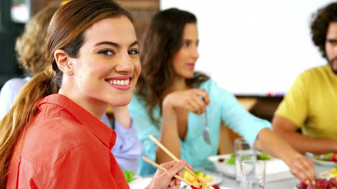 Portrait of woman having lunch while colleague interacting in background Footage