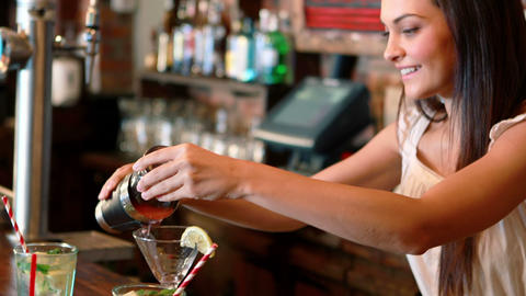Barmaid pouring cocktail in glass at bar counter Footage