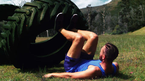 Man performing leg workout with tire at boot camp Footage