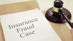 Insurance fraud written on legal documents with gavel Footage