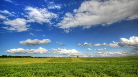 Timelapse clouds over the green field Stock Video Footage