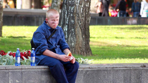 Teen eats in the streets 1 Stock Video Footage