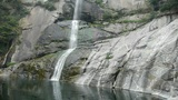 waterfall on cliffs in mountains,flowing into pond lake Footage