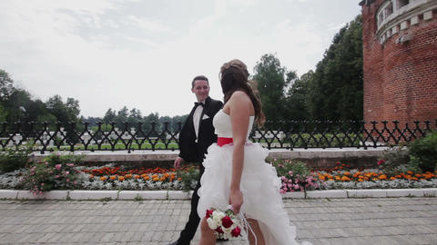 Newly married couple walk on park holding hands Footage