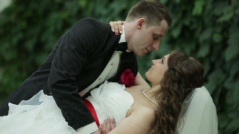 Groom holds his bride in his arms Footage