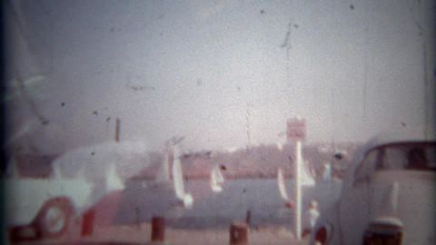 1966: Leaving parking space with view of sailboats in harbor. SAN DIEGO, CALIFOR Footage
