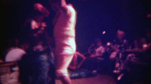 1973: Embarrassed drunk tourists learning hula dancing rope spinning on stage. H Footage