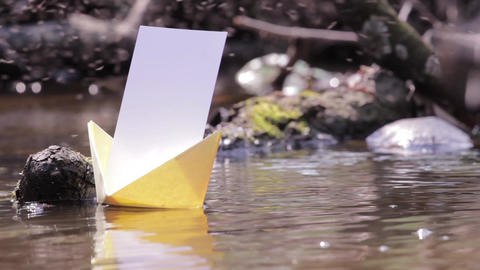 Yellow paper boats floating on the muddy water of ponds 77a Footage