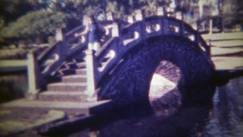 1973: Women crossing japanese garden style bridge over troubled water. HONOLULU, Live Action