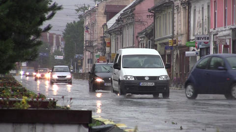 Column Of Cars At Low Speed While Passing Through The Center Of Town While It Ra stock footage