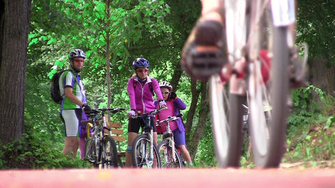Group of bicyclists make a halt in the woods while other riders passed by them 5 Footage