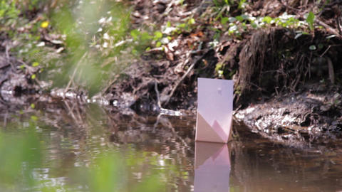 Paper prow floating adrift on the water of a river 65a Footage