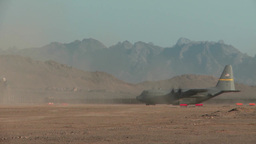 C-130 Hercules plane taxing for takeoff on a dusty airfield Footage
