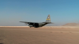 C-130 Hercules taking off from dusty air strip Footage