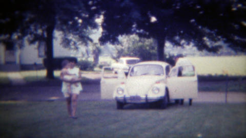 1971: Family arrives in Volkswagen Beetle Bug car parks on lawn. DES MOINES, IOW Footage